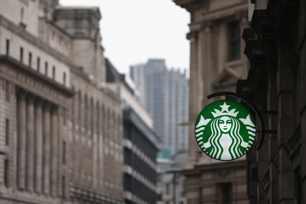 LONDON, ENGLAND - JANUARY 25:  A sign for a branch of Starbucks coffee is illuminated at dusk in the City of London on January 25, 2013 in London, England. .  (Photo by Oli Scarff/Getty Images)